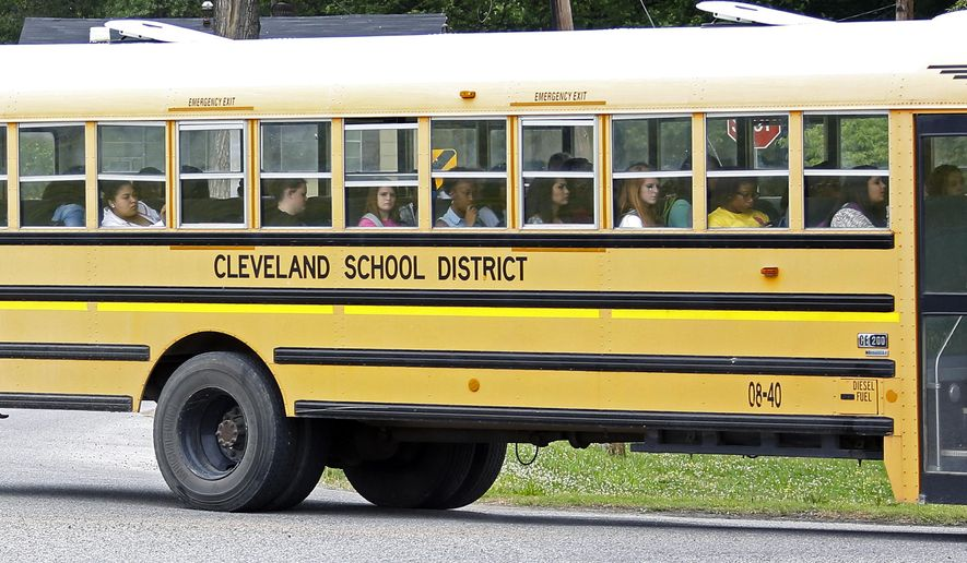 In this May 13, 2015 photo, an integrated group of Cleveland, Miss., public school students ride the bus on their way home following classes. On Monday, May 18, a five-day federal court hearing starts in Jackson and could settle whether Cleveland's two middle schools and two high schools are merged as one each as part of a 49-year-old desegregation lawsuit. (AP Photo/Rogelio V. Solis)