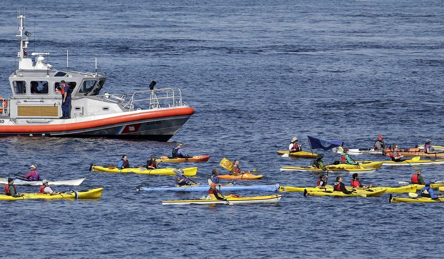 A small flotilla of kayakers protesting the oil drilling rig Polar Pioneer are followed by a U.S. Coast Guard boat Thursday, May 14, 2015, in Elliott Bay in Seattle. The rig is the first of two drilling rigs Royal Dutch Shell is outfitting for oil exploration and was towed to the Port of Seattle site despite the city's warning that it lacks permits and threats by kayaking environmentalists to paddle out in protest. (AP Photo/Elaine Thompson)