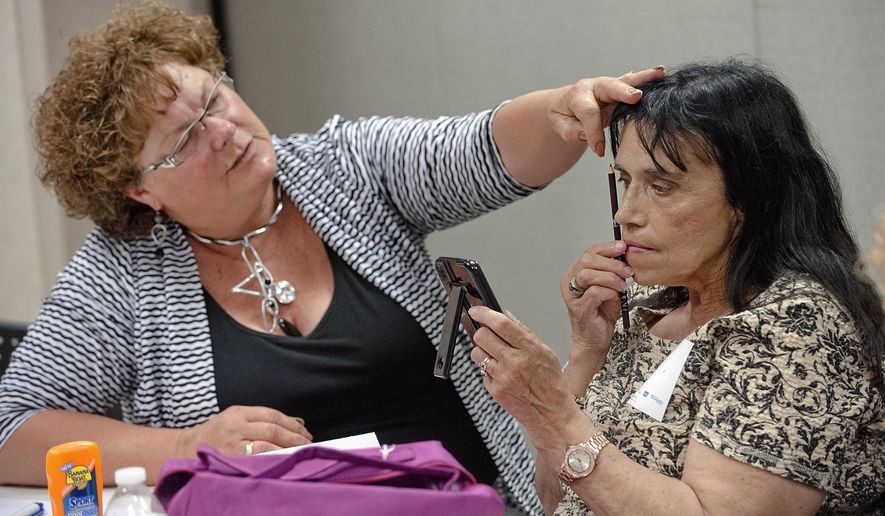 ADVANCE FOR THE WEEKEND OF MAY 16-17 AND THEREAFTER - In a Monday, May, 4, 2015 photo, volunteer cosmetologist Diana Heeney, left, demonstrates the skill of drawing eyebrows with Angela Jones of Sloan during the Look Good Feel Better program at June E. Nylen Cancer Center in Sioux City, Iowa. The free program connects volunteer cosmetologists with cancer patients who are looking to improve their style and self-image. (Justin Wan/Sioux City Journal via AP)