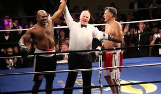 Five-time heavyweight boxing champion Evander Holyfield, left, is declared the winner against Former Republican presidential candidate Mitt Romney during a charity fight night event Friday, May 15, 2015, in Salt Lake City. The black-tie event raised money for the Utah-based organization CharityVision, which helps doctors in developing countries perform surgeries to restore vision in people with curable blindness. (Kristin Murphy/Deseret News via AP) SALT LAKE TRIBUNE OUT;  MAGS OUT