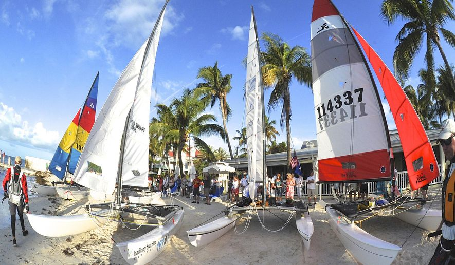 In this photo provided by the Florida Keys News Bureau, five 16-foot-long Hobie Cat sailboats line South Beach in Key West, Fla., Saturday, May 16, 2015,  prior to the beginning of the  Havana Challenge. The more than 90-mile-long race is believed to be the first U.S. government-sanctioned sailing regatta between Key West and Cuba in more than 50 years. (Bert Budde/Florida Keys News Bureau via AP)