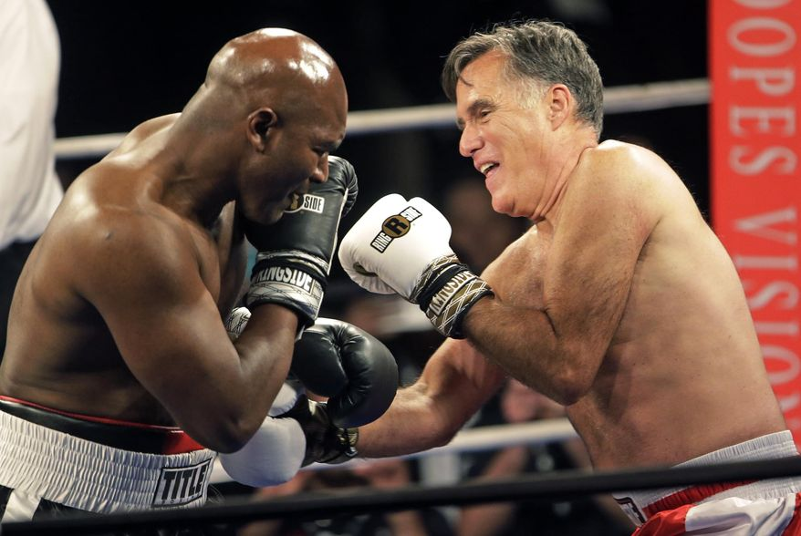 Former Republican presidential candidate Mitt Romney, right, throws punches with five-time heavyweight boxing champion Evander Holyfield at a charity fight night event Friday, May 15, 2015, in Salt Lake City. The black-tie event will raise money for the Utah-based organization CharityVision, which helps doctors in developing countries perform surgeries to restore vision in people with curable blindness. (AP Photo/Rick Bowmer)