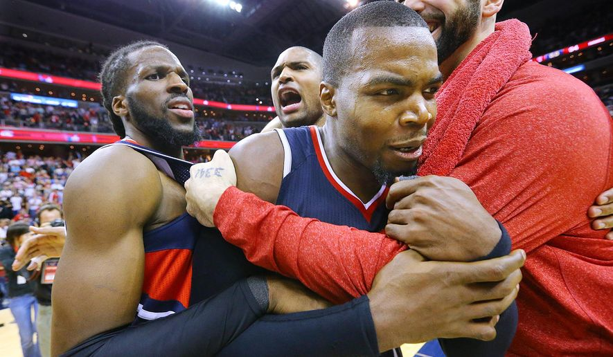 Atlanta Hawks' DeMarre Carroll, Al Horford, Paul Millsap and Pero Antic, from left, celebrate after the Hawks defeated the Washington Wizards 94-91 in Game 6 of an NBA basketball playoffs second-round series, Friday, May 15, 2015, in Washington. The win sent the Hawks to the Eastern Conference finals. (Curtis Compton/Atlanta Journal-Constitution via AP)