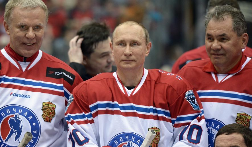 Russian President Vladimir Putin, center, flanked by Defense Minister Sergei Shoigu, right, and Chairman of the Federation Council's Commission on sports, Vyacheslav Fetisov, pose for a photograph,  after an exhibition hockey game at the Night Hockey League tournament in the Black Sea resort of Sochi, Russia, Saturday, May 16, 2015. President Vladimir Putin has played in an exhibition hockey game and scored one goal after another on assists from retired NHL players. (Alexei Nikolsky/RIA-Novosti, Kremlin Pool Photo via AP)