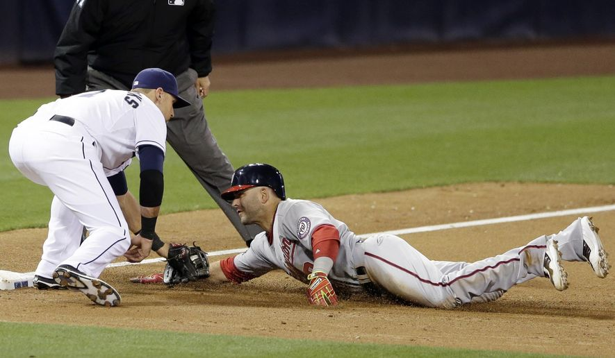 Washington Nationals' Danny Espinosa, right, is tagged out by San Diego Padres third baseman Will Middlebrooks while trying to reach third during the third inning in a baseball game Friday, May 15, 2015, in San Diego. (AP Photo/Gregory Bull)
