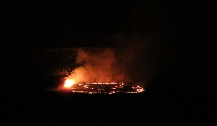 In this Saturday, May 9, 2015 photo, molten rock lights up the night as it spews into a lake of lava near the summit of Kilauea volcano on Hawaii's Big Island. The lava lake had reached a record high level on May 8 and then began descending, making scientists wonder where the molten rock will go next. (AP Photo/Cathy Bussewitz)