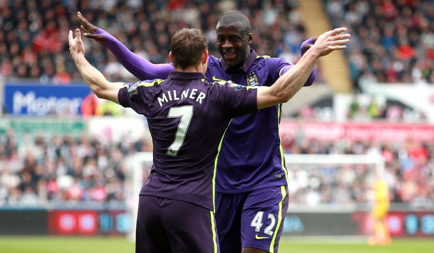 Manchester City's Yaya Toure, right, celebrates scoring his side's first goal of the game with teammate James Milner during their English Premier League soccer match against Swansea City at the Liberty Stadium, Swansea, Wales, Sunday, May 17, 2015. (David Davies/PA via AP)    UNITED KINGDOM OUT      -    NO SALES     -     NO ARCHIVES
