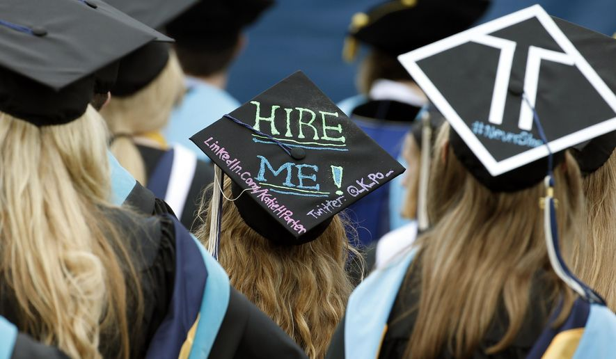George Washington University graduates, including one looking for a job, are seated during the school's commencement exercises on the National Mall, Sunday, May 17, 2015 in Washington. (AP Photo/Alex Brandon)  ** FILE **
