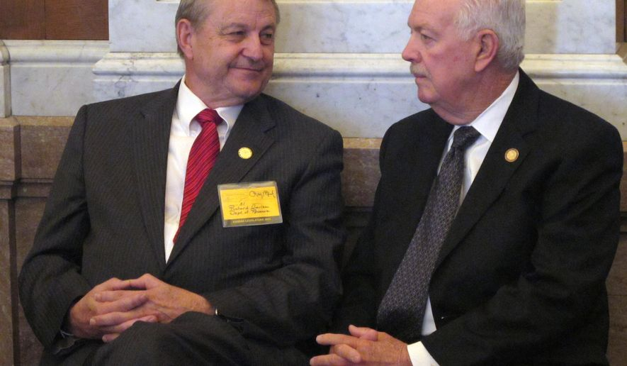 In this Friday, May 15, 2015 photo, Richard Carlson, left, legislative liaison for the Kansas Department of Revenue, visits with state House Speaker Ray Merrick during a debate in the chamber on tax issues at the Statehouse in Topeka, Kan. Carlson is a former House Taxation Committee chairman. (AP Photo/John Hanna)