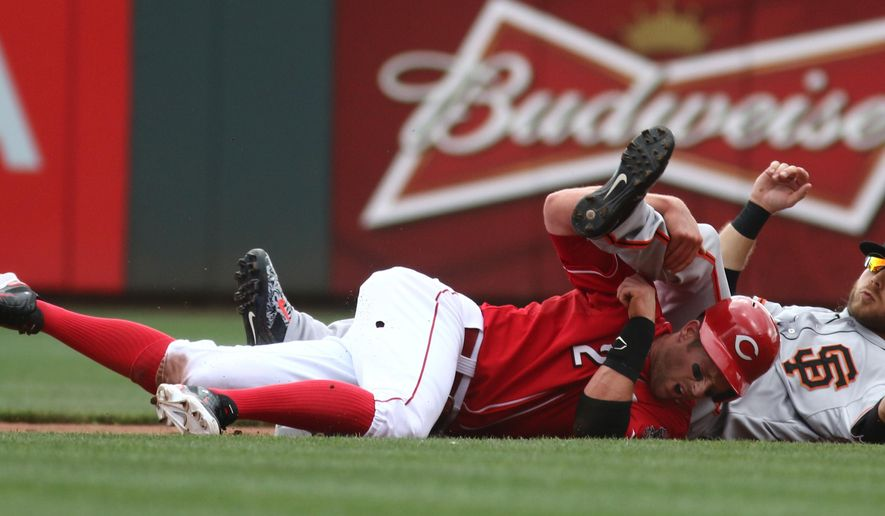 Cincinnati Reds Zack Cozart gets forced out at second base as San Francisco Giants Brandon Crawford falls over him in the first inning of a baseball game in Cincinnati, Sunday, May 17, 2015. (AP Photo/Tom Uhlman)