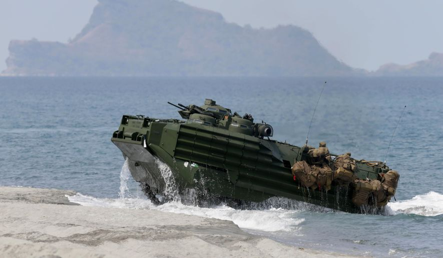 FILE - In this April 21, 2015 file photo, an amphibious assault vehicle with Philippine and U.S. troops on board storms a beach during an annual U.S.-Philippines joint military drill at the Naval Education and Training Command at San Antonio township, Zambales province, northwest of Manila, Philippines. Amphibious military capabilities are on the agenda the week of May 18, 2015, as the U.S. Marine Corps and Navy host defense leaders from around the Pacific in Hawaii. (AP Photo/Bullit Marquez, File)