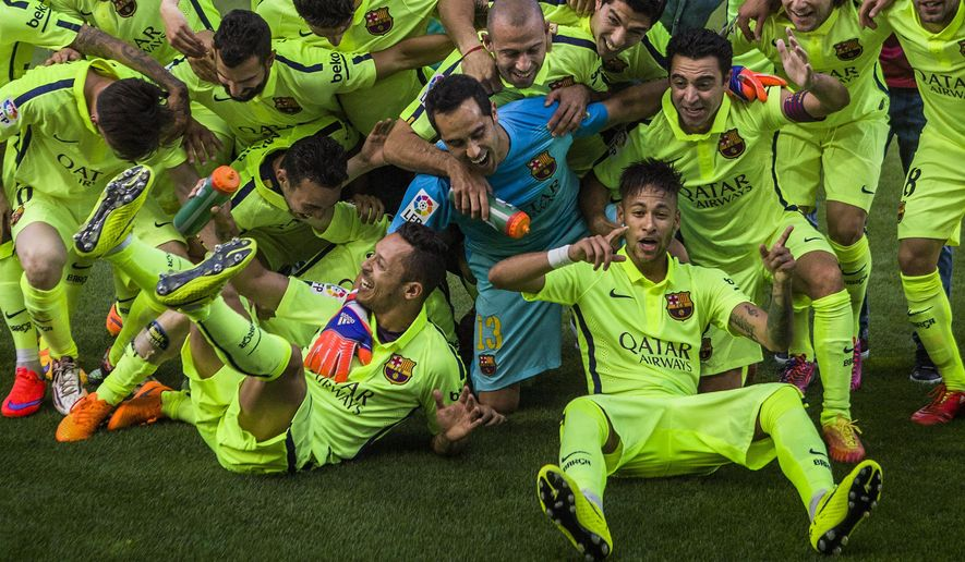 Barcelona's players celebrate their championship after a Spanish La Liga soccer match between Atletico Madrid and FC Barcelona at the Vicente Calderon stadium in Madrid, Spain, Sunday, May 17, 2015. (AP Photo/Andres Kudacki)