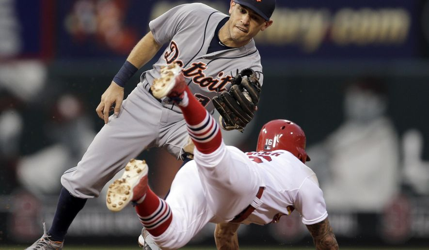 Detroit Tigers second baseman Ian Kinsler, top, prepares to tag St. Louis Cardinals' Kolten Wong out at second on a failed steal attempt during the second inning of a baseball game, Sunday, May 17, 2015, in St. Louis. (AP Photo/Jeff Roberson)