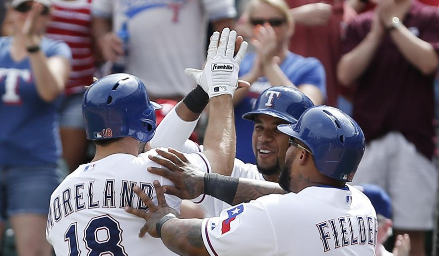 Texas Rangers' Mitch Moreland (18) is congratulated by Elvis Andrus, center, and designated hitter Prince Fielder (84) after hitting a two-run home run during the sixth inning of a baseball game against the Cleveland Indians, Sunday, May 17, 2015, in Arlington, Texas. (AP Photo/Brandon Wade)