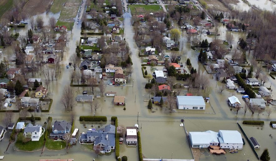 FILE - This Friday May 6, 2011 file photo shows an aerial view of the flooded areas along the Richelieu River in St-Jean-sur-Richelieu, Quebec, Canada. The International Joint Commission hopes to begin a $14 million study to determine if there is any way to control spring flooding in Lake Champlain and the Richelieu River in Quebec. The study stems from the historic 2011 spring flooding that kept the lake and the river above flood stage for two months, inundating low-lying parts of Saint Jean Sur Richelieu, Quebec, about 20 miles north of the US border. (AP Photo/The Canadian Press via AP. File)