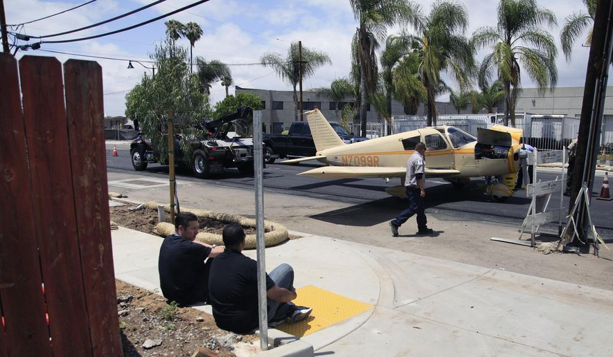 The pilot and passenger watch from the sidewalk as their small aircraft prepares to be towed, Saturday, May 16, 2015 in Santee, Calif. The pilot had to make an emergency landing near Cuyamaca Street and Prospect Avenue in Santee Saturday. No injuries were reported. (Misael Virgen/U-T San Diego via AP)  NO SALES; COMMERCIAL INTERNET OUT; MANDATORY CREDIT
