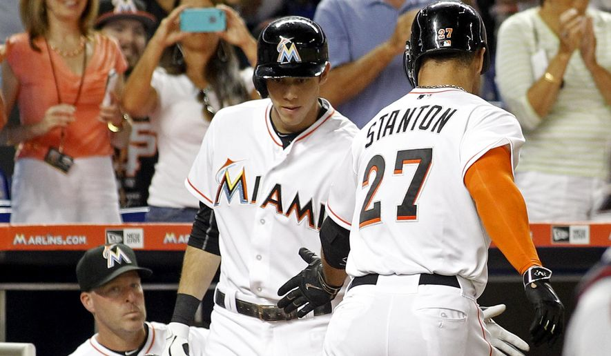 Miami Marlins' Giancarlo Stanton (27) is congratulated by teammate Christian Yelich, center, as manager Mike Redmond watches after hitting a third-inning solo home run against the Atlanta Braves during a baseball game in Miami, Friday, May 15, 2015. (AP Photo/Joe Skipper)