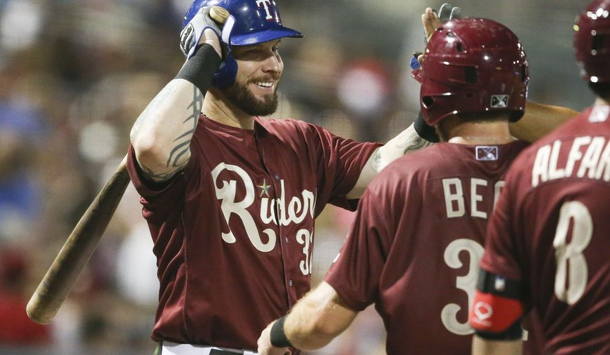 Texas Rangers' Josh Hamilton congratulates teammate Preston Beck for scoring against the Corpus Christ Hooks, during a rehab baseball game with the Frisco RoughRiders, Saturday, May 16, 2015, in Frisco, Texas. (Jim Cowsert/Fort Worth Star-Telegram via AP)