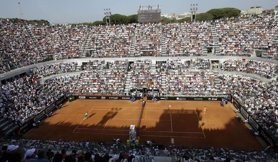 "Serbia's Novak Djokovic, right, plays Switzerland's Roger Federer during their final match at the Italian Open tennis tournament, in Rome, Sunday, May 17, 2015. Running out of room and with ticket demand soaring, local organizers want to move the Italian Open from its historic Foro Italico venue to a new location near Rome's main airport. ""We can't fit in here anymore,"" Italian tennis federation president Angelo Binaghi said Sunday. ""The hunger for tennis makes this the biggest sports event in Italy."" The 10,500-seat Foro Italico stadium, inaugurated in 2010, isn't big enough, Binaghi added. (AP Photo/Alessandra Tarantino)"