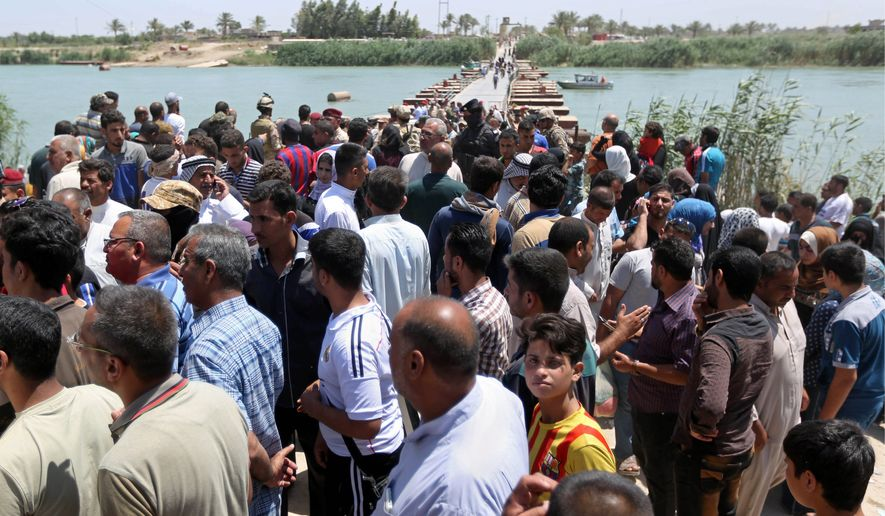 Iraqis from Ramadi gathered at the Bzebiz bridge after fleeing Ramadi and spending the night walking toward Baghdad on Saturday. Islamic State militants seized the center of their city in western Iraq, but U.S. officials say the takeover is only temporary. (Associated Press)