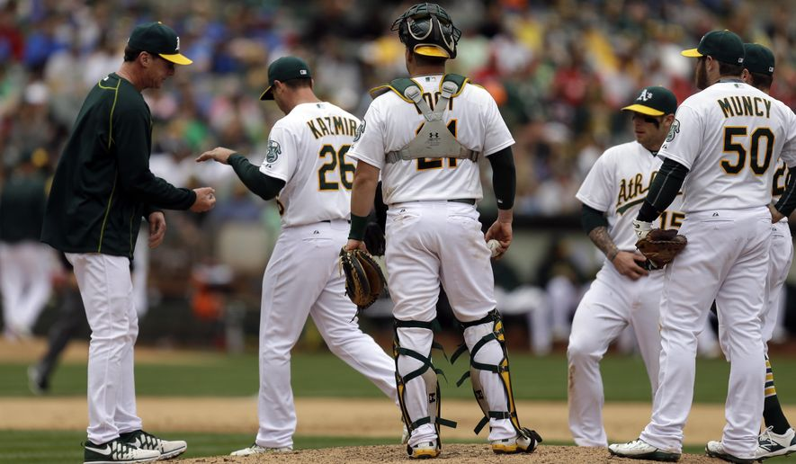 Oakland Athletics manager Bob Melvin, left, accepts the ball from pitcher Scott Kazmir in the fifth inning of a baseball game against the Chicago White Sox, Sunday, May 17, 2015, in Oakland, Calif. (AP Photo/Ben Margot)