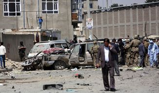 U.S. and Afghan security forces inspect the site of suicide attack near an international airport in Kabul, Afghanistan, Sunday, May 17, 2015. A suicide bomber detonated an explosives-packed car near Kabul's international airport on Sunday, wounding at least 16 civilians in an attack that may have been aimed at vehicles of the European Union Police Mission in Afghanistan, officials said. (AP Photo/Rahmat Gul)