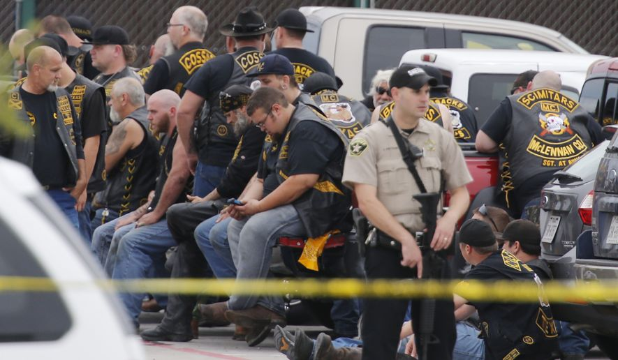 """A McLennan County deputy stands guard near a group of bikers in the parking lot of a Twin Peaks restaurant Sunday, May 17, 2015, in Waco, Texas. Waco Police Sgt. W. Patrick Swanton told KWTX-TV there were """"multiple victims"""" after gunfire erupted between rival biker gangs at the restaurant. (Rod Aydelotte/Waco Tribune-Herald via AP)"""