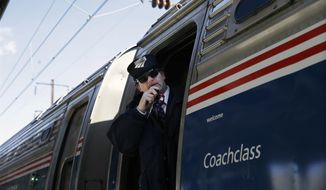 Amtrak conductor Michael Laubauskas talks on a radio in Trenton, N.J. as his train departs for Washington, D.C. (Associated Press)
