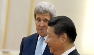 U.S. Secretary of State John Kerry, left, looks at Chinese President Xi Jinping as he introduces his accompanying staff to Xi at the Great Hall of the People at the Great Hall of the People in Beijing, China, Sunday, May 17, 2015. Kerry was meeting Sunday with Chinese President Xi before heading to South Korea to complete a short Asian tour that has been clouded so far by concerns over China's construction in South China Sea.  (Kim Kyung-Hoon/Pool Photo via AP)