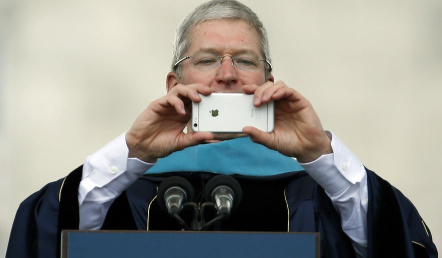 Apple CEO Tim Cook takes a picture with his iPhone while addressing graduates during George Washington University's commencement exercises on the National Mall, Sunday, May 17, 2015 in Washington. The university awarded Cook with an honorary doctorate of public service. (AP Photo/Alex Brandon)