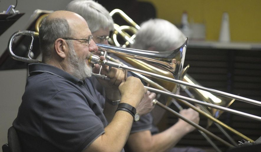 ADVANCE FOR USE SUNDAY, MAY 17 - In this photo taken April 22, 2015, Randy Neuharth plays with the Norfolk Area Jazz Ensemble during a practice at Northeast Community College in Norfolk, Neb. During the day, they teach and attend school, treat patients and perform a variety of other important tasks. But once a week, they put down their dental drills and stethoscopes, leave their classrooms and instead pick up their trombones, trumpets and saxophones to make music. (Jake Wragge, The Norfolk Daily News via AP)