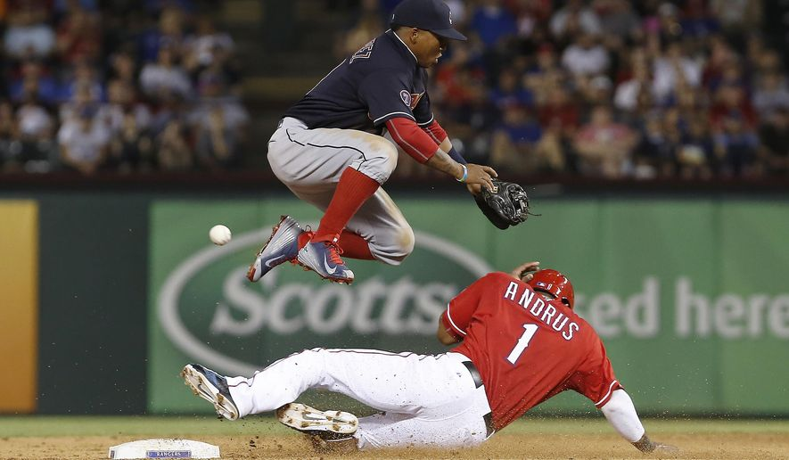 Cleveland Indians shortstop Jose Ramirez, top, is unable to catch the throw from catcher Roberto Perez as Texas Rangers' Elvis Andrus (1) steals second base during the fifth inning of a baseball game, Saturday, May 16, 2015, in Arlington, Texas. The throw got past Ramirez and into the outfield to allow Andrus to score on the play. (AP Photo/Brandon Wade)