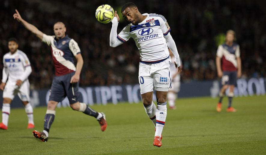 Lyon's Alexandre Lacazette heads the ball, during the French League One soccer match between Lyon and Bordeaux, in Lyon, central France, Saturday, May 16, 2015. (AP Photo/Laurent Cipriani)
