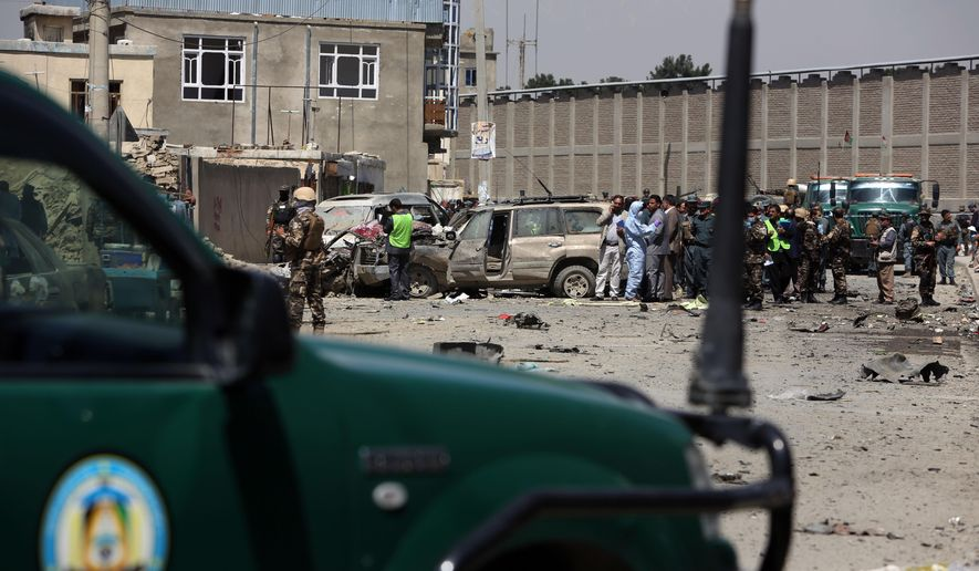 Afghan security forces inspect the site of suicide attack near an international airport in Kabul, Afghanistan, Sunday, May 17, 2015. A suicide bomber detonated an explosives-packed car near Kabul's international airport on Sunday, wounding at least 16 civilians in an attack that may have been aimed at vehicles of the European Union Police Mission in Afghanistan, officials said. (AP Photo/Rahmat Gul)
