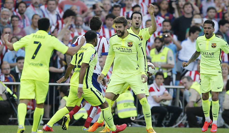Barcelona players celebrate after the final whistle during a Spanish La Liga soccer match between Atletico Madrid and Barcelona at the Vicente Calderon stadium in Madrid, Spain, Sunday May 17, 2015. Barcelona won the match 1-0 to be proclaimed league champions. (AP Photo/Paul White)