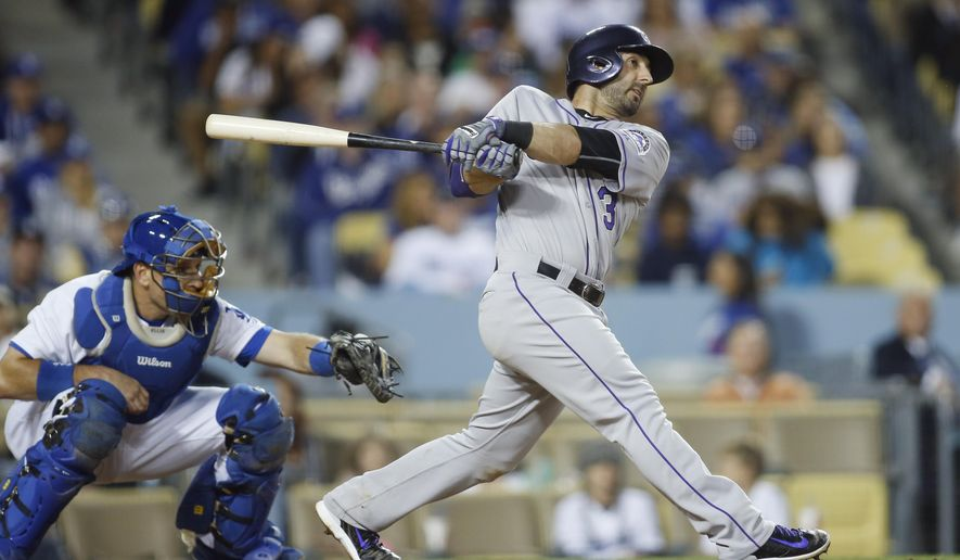 Colorado Rockies' Daniel Descalso, right, hits a two-run home run in front of Los Angeles Dodgers catcher A.J. Ellis, left, to also drive in teammate Michael McKenry during the seventh inning of a baseball game, Saturday, May 16, 2015, in Los Angeles. (AP Photo/Danny Moloshok)