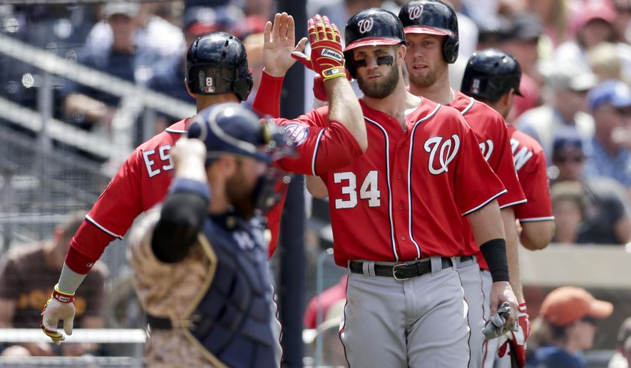Washington Nationals' Danny Espinosa, left, is greeted by teammates Bryce Harper (34), and Stephen Strasburg, right, after hitting a three-run home run against the San Diego Padres during the fifth inning in a baseball game, Sunday, May 17, 2015, in San Diego. (AP Photo/Gregory Bull)