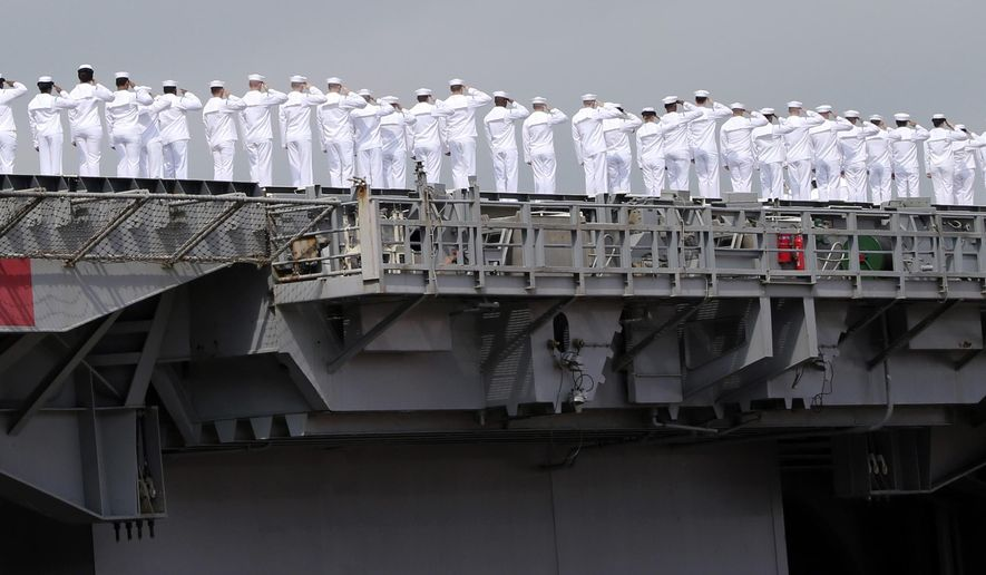 Sailors of USS George Washington salute as they leave the U.S. Navy's Yokosuka base in Yokosuka, near Tokyo Monday, May 18, 2015. The U.S. Navy's Japan-based aircraft carrier is heading home after seven years, to be replaced by a newer version of the same ship in the fall. (AP Photo/Koji Sasahara)