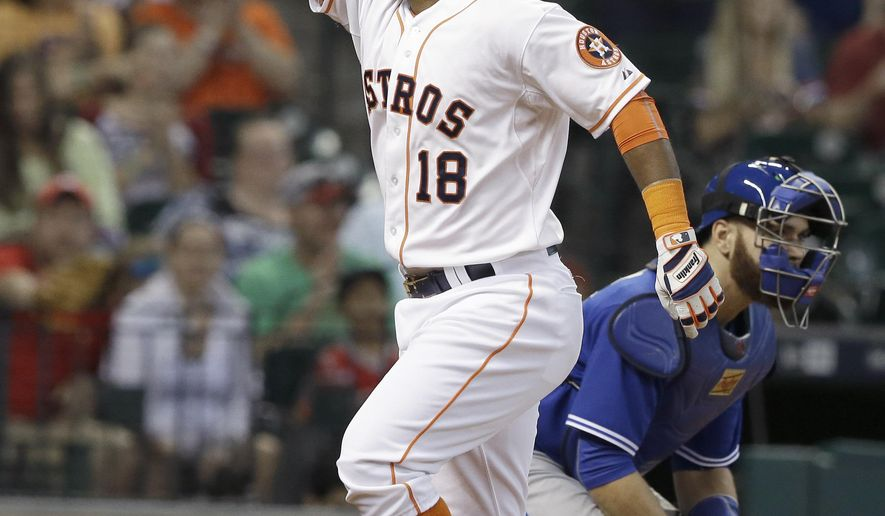 Houston Astros' Luis Valbuena (18) points to the stands as he crosses home plate to score on a solo homerun beside Toronto Blue Jays catcher Russell Martin in the first inning of a baseball game, Sunday, May 17, 2015, in Houston. (AP Photo/Pat Sullivan)