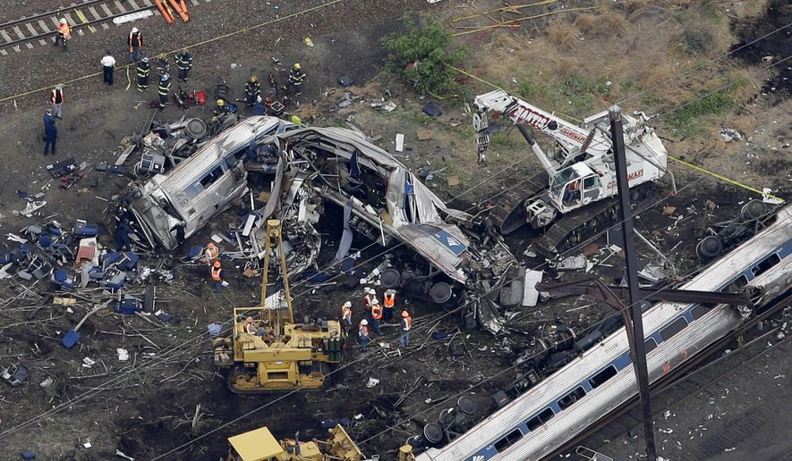 In this aerial photo taken May 13, 2015, emergency personnel work at the scene of a deadly train wreck in Philadelphia. Amtrak faces what probably will be a $200 million payout to crash victims _ the cap established by Congress nearly 20 years ago as part of a compromise to rescue the railroad from financial ruin. It would be the first time that the liability ceiling, considered by many to be too low to cover the costs of the eight lives lost and 200 people injured, designed for Amtrak actually would apply to the railroad.  (AP Photo/Patrick Semansky)