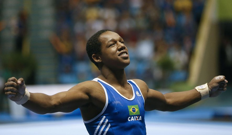 In this May 2, 2015 photo, Angelo Assumpcao of Brazil competes during the Gymnastic World Challenge 2015 in Sao Paulo, Brazil. The Brazilian confederation of gymnastics is investigating racial remarks made by members of the men's team toward a black teammate seen in a video that surfaced early May 2015. The gymnasts were seen telling fellow athlete Assumpcao that a smartphone's screen is white when it works and black when it doesn't; that supermarkets' bags are white and trash bags black. (AP Photo/Andre Penner)