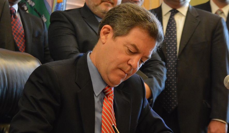 Kansas Gov. Sam Brownback signs legislation overhauling how the state collects taxes from businesses to finance benefits for unemployed workers, Monday, May 18, 2015, at the Statehouse in Topeka, Kan. The new law is designed to make businesses' taxes more predictable and sets a new maximum cap on weekly benefits. (AP Photo/Nicholas Clayton)