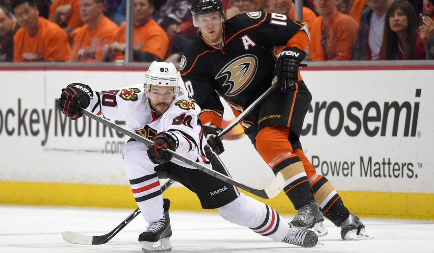 Chicago Blackhawks center Antoine Vermette, left, passes the puck under pressure from Anaheim Ducks right wing Corey Perry during the second period in Game 1 of a Western Conference finals hockey series, Sunday, May 17, 2015, in Anaheim, Calif. (AP Photo/Mark J. Terrill)