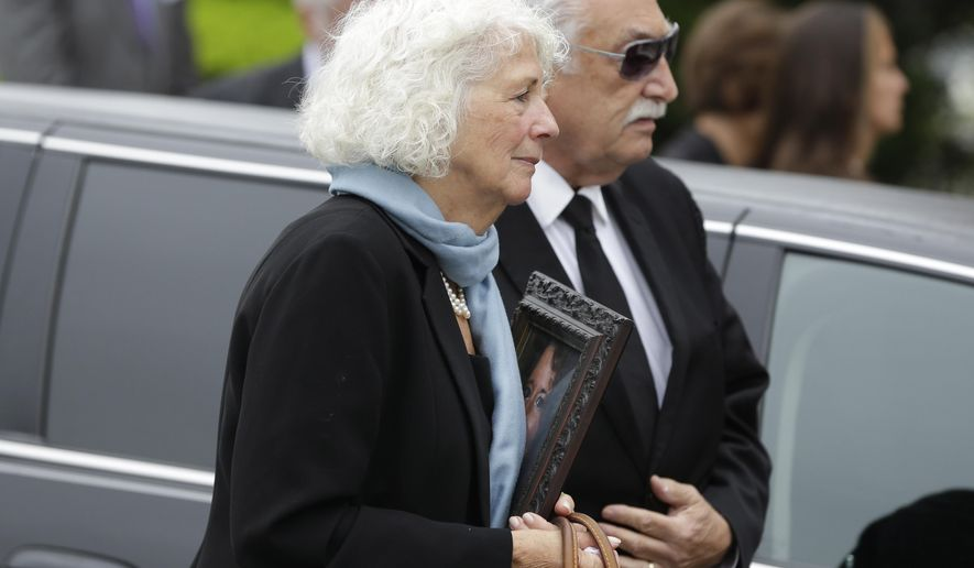 A family member carries a picture of Laura Finamore, who was killed in the May 12 Amtrak train derailment in Philadelphia, into the church during her funeral in New York, Monday, May 18, 2015. Finamore, 47, was returning to New York City from a memorial service for a college friend's mother. (AP Photo/Seth Wenig)