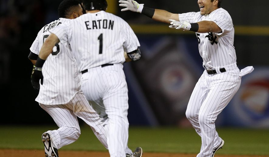 Chicago White Sox's Carlos Sanchez, right, celebrates with Melky Cabrera, left,  and Adam Eaton, center, after knocking in the game-winning run during the tenth inning of a baseball game Monday, May 18, 2015, in Chicago. The Chicago White Sox won 2-1. (AP Photo/Andrew A. Nelles)
