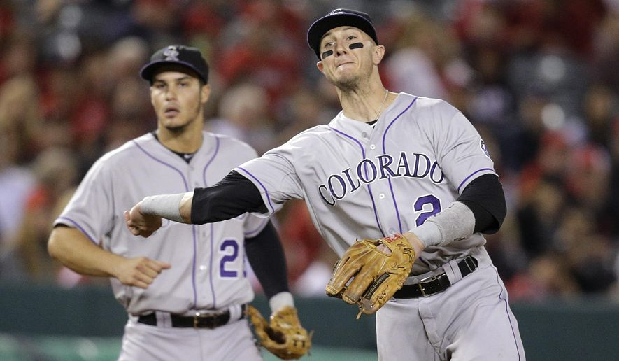 Colorado Rockies shortstop Troy Tulowitzki throws the ball to first base for the out on Los Angeles Angels' Johnny Giavotella as third baseman Nolan Arenado watches during the sixth inning of a baseball game, Tuesday, May 12, 2015, in Anaheim, Calif. (AP Photo/Jae C. Hong)
