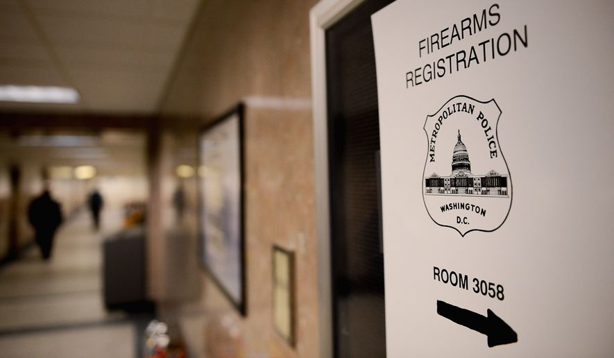 Signs direct people to the office of the Firearms Registration Unit at the District's Metropolitan Police Department headquarters. (The Washington Times)