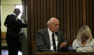 Retired tennis player Bob Hewitt, left, with his wife Delaille Hewitt, right, sit inside ahead of his sentencing at the high court in Pretoria, South Africa, Monday, May 18, 2015.  Hewitt, a former Grand Slam doubles tennis champion, was convicted in South African court of rape and sexual assault decades after the alleged assaults, and sentenced to six years in prison.  (AP Photo/Themba Hadebe)