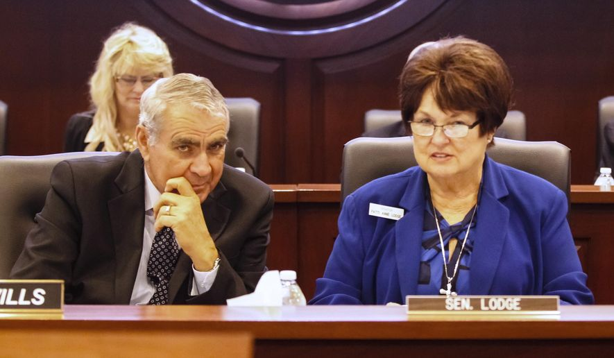 """Rep. Richard """"Rich"""" Wills, R-Glenns Ferry, and Sen. Patti Anne Lodge, R-Huston, confer before a joint session of the Senate Judiciary and Rules and the House Judiciary, Rules, and Administration committees during a special session of the Idaho legislature at the state Capitol building on Monday, May 18, 2015 in Boise, Idaho. (AP Photo/Otto Kitsinger)"""