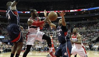 Washington Wizards guard John Wall (2) passes the ball in front of Atlanta Hawks forward Paul Millsap (4) and center Al Horford (15), from the Dominican Republic, in the second half of Game 6 of the second round of the NBA basketball playoffs, Friday, May 15, 2015, in Washington.  The Hawks won 94-91 to advance to the next round. (AP Photo/Alex Brandon)